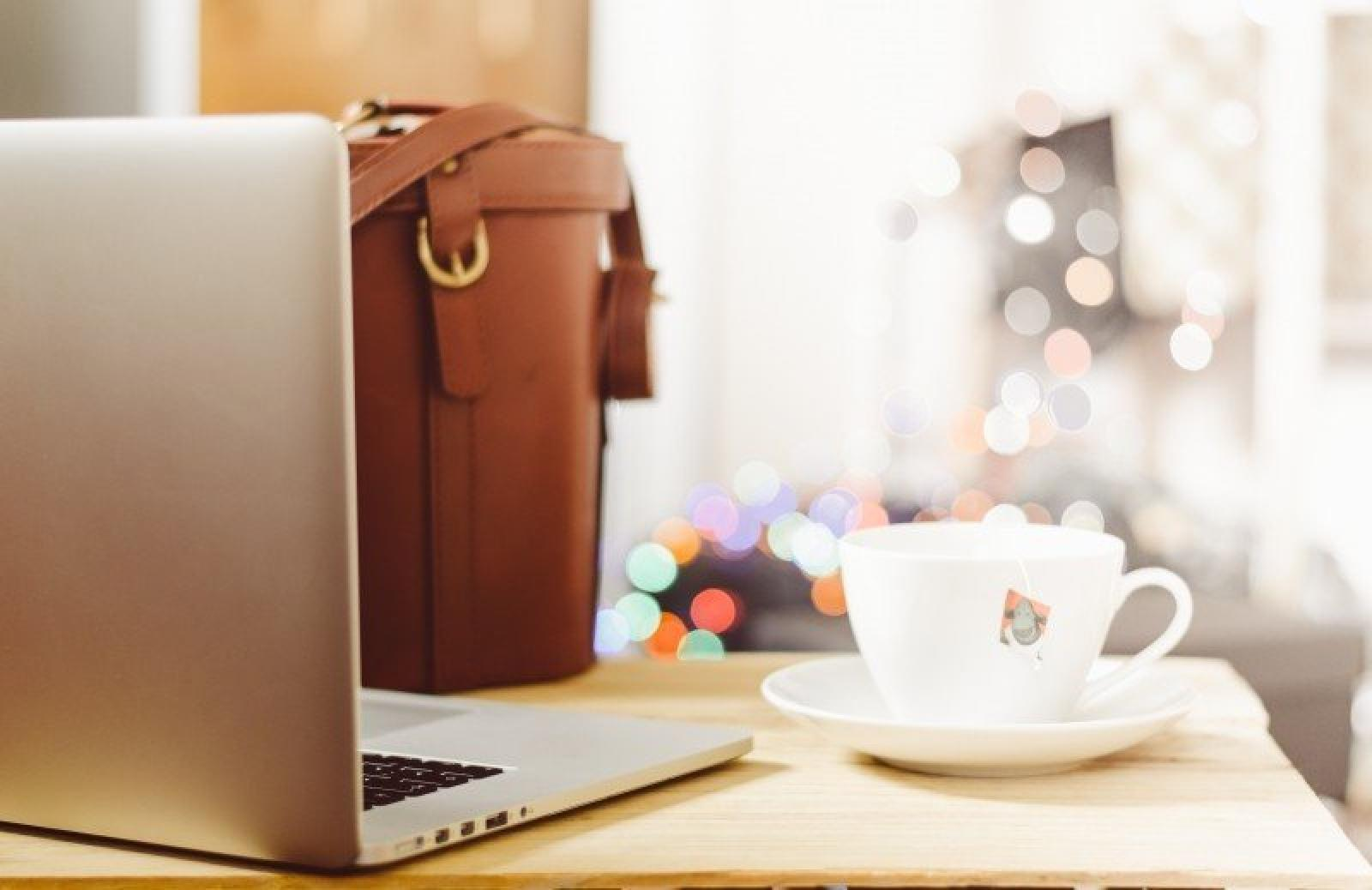 coffee cup and laptop with handbag on table