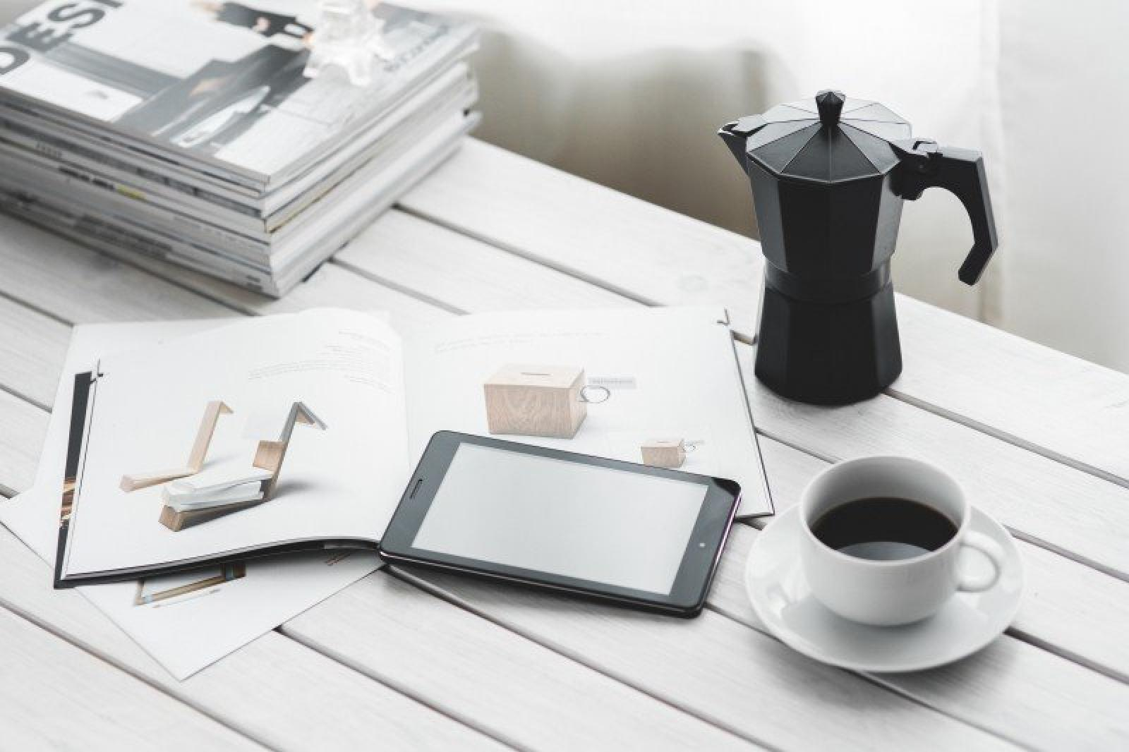 coffee percolator coffee cup digital tablet and magazines on white table