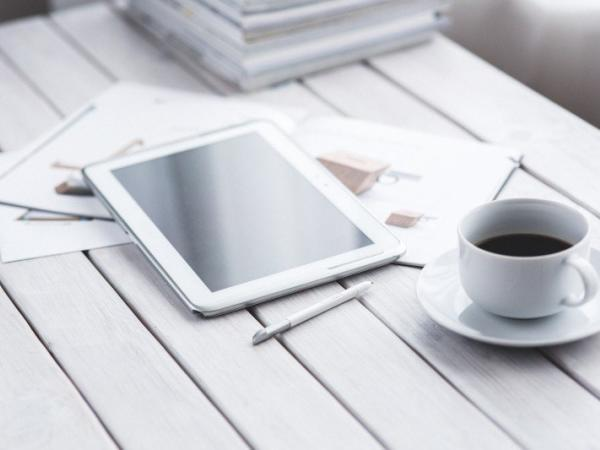 coffee cup and digital tablet on wooden table