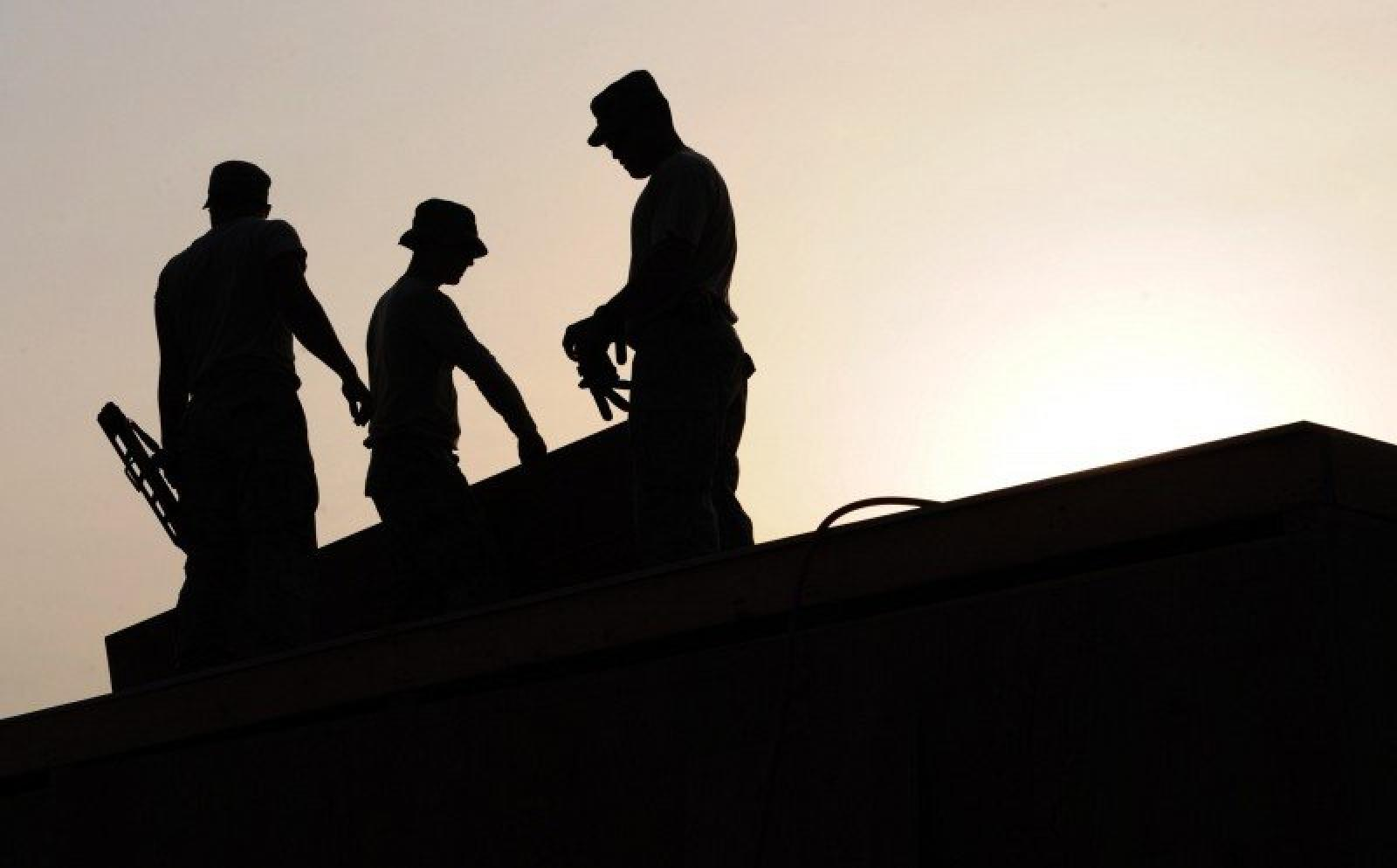 silhouette of workers on construction site