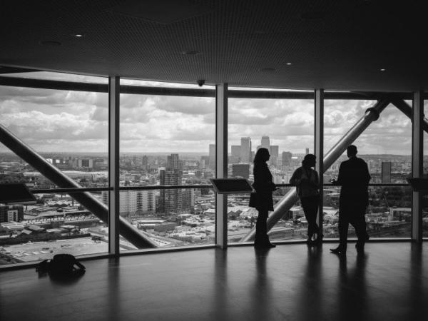 black and white image of colleagues standing in office and looking at city view through window